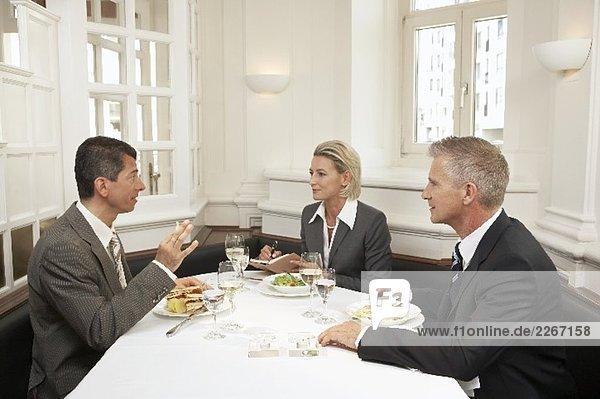 Drei Geschäftsleute bei einem gemeinsamen Essen