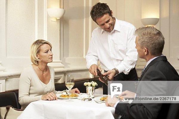 Kellner würzt einem Mann das Essen im Restaurant