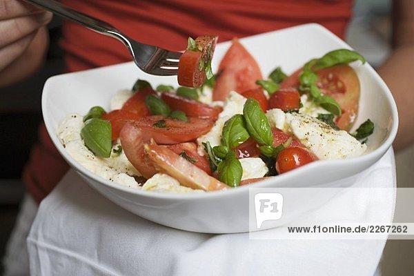 Frau isst Tomaten mit Mozzarella und Basilikum