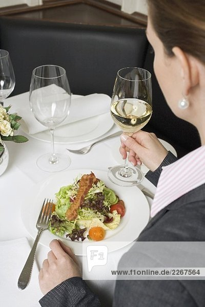 Frau trinkt Weisswein zum Salat im Restaurant
