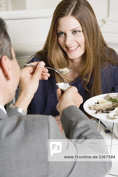 Man offering woman fresh oyster in restaurant