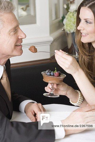 Frau reicht Mann Löffel mit Schokoladencreme im Restaurant