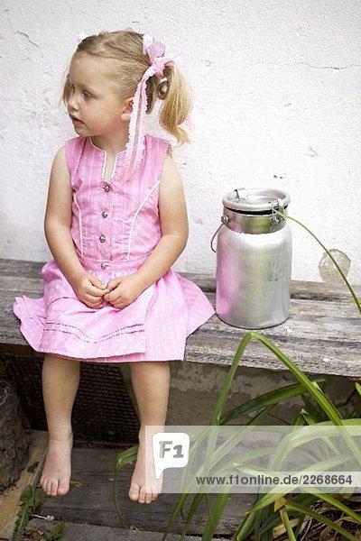 Kleines Mädchen auf Holzbank mit Milchkanne