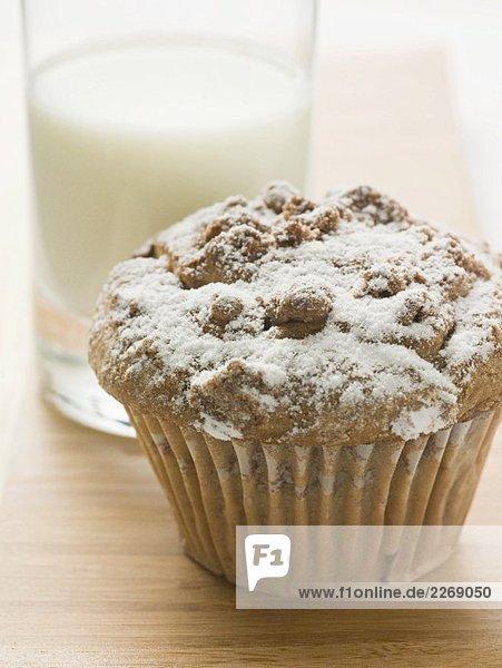 Nussmuffin mit Puderzucker vor Glas Milch