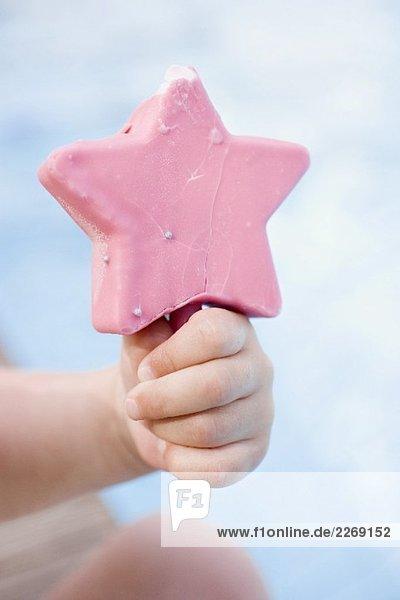 Kinderhand hält rosa Eis am Stiel Kinderhand hält rosa Eis am Stiel