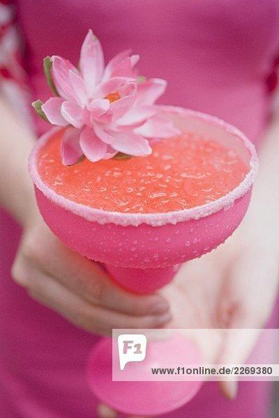 Frau hält pinkfarbenes Glas mit Cocktail  dekoriert mit Blüte Frau hält pinkfarbenes Glas mit Cocktail, dekoriert mit Blüte