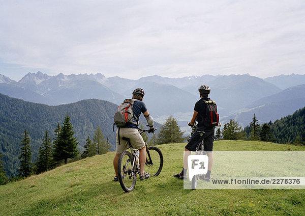Zwei Radfahrer auf einem Hügel mit Blick auf die Aussicht