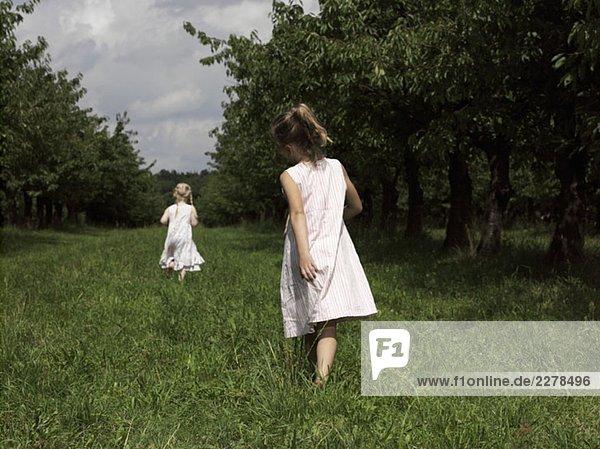 Zwei Mädchen,  die durch ein Feld laufen.