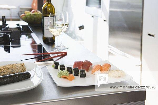 Sushi und Weißwein auf einer Küchenbank