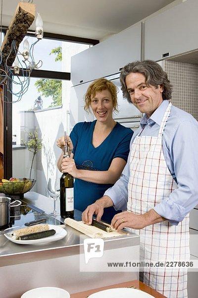 Ein Paar bereitet das Abendessen in der Küche vor.