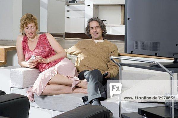 Eine Frau  die ein Handy neben einem Mann benutzt  der fernsieht.