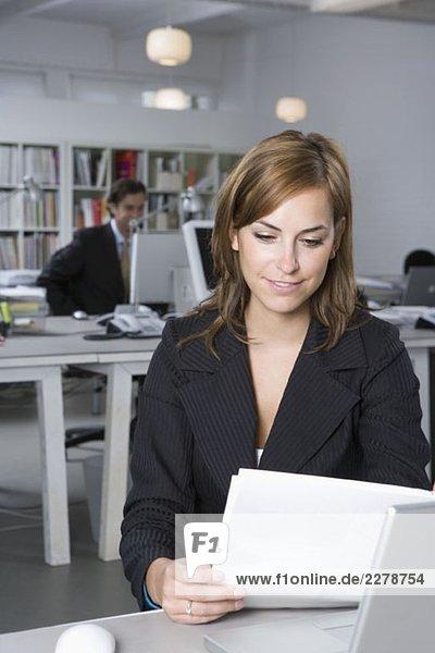 Eine Frau  die sich ein Dokument ansieht  während sie an einem Schreibtisch im Büro sitzt.
