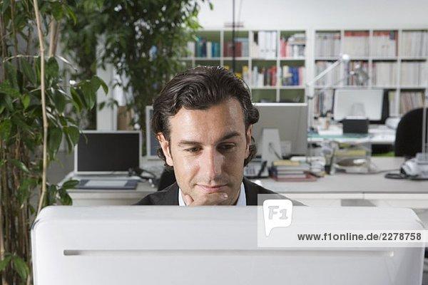 Ein Geschäftsmann  der einen Computer in einem Büro benutzt.