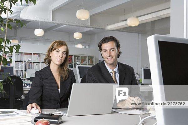 Bürokollegen sitzen Seite an Seite am Schreibtisch