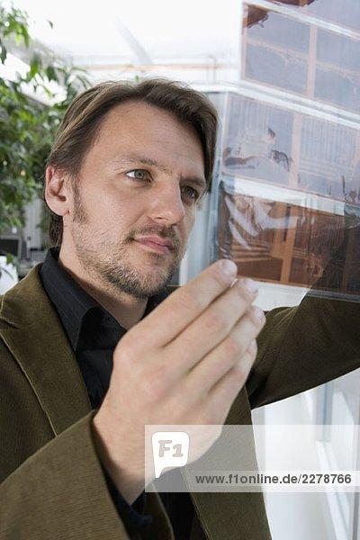 Ein Mann  der auf ein Gleitkontaktblatt schaut