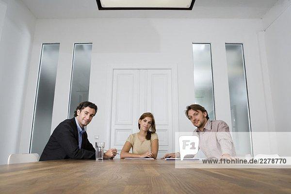 Drei Personen sitzen an einem Tisch im Konferenzraum