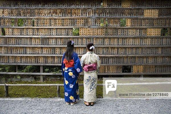 Two woman wearing kimonos reading prayer blocks