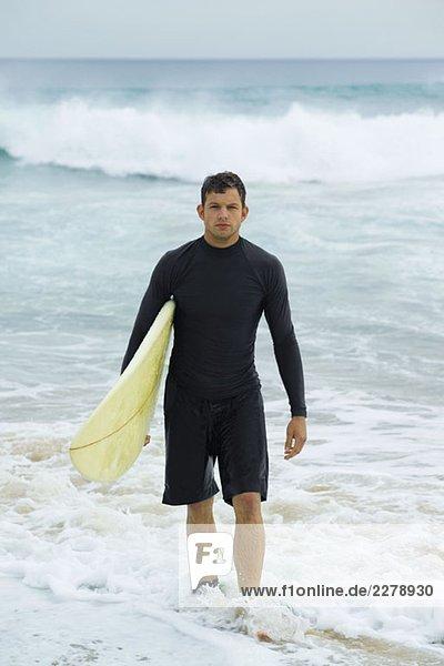 Ein Surfer mit seinem Surfbrett