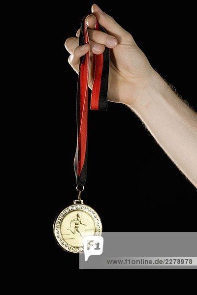 Eine Hand mit einer Goldmedaille