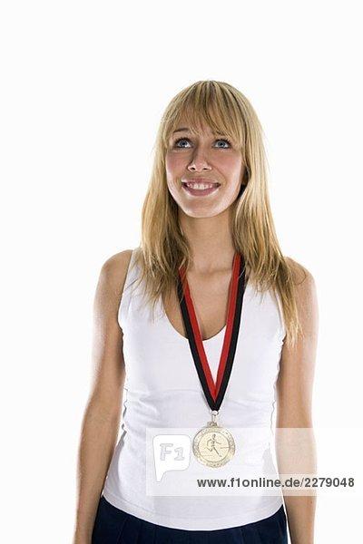 Eine Frau  die eine Goldmedaille trägt und lächelt.