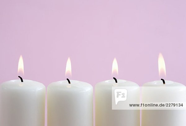 Vier brennende Kerzen in einer Reihe