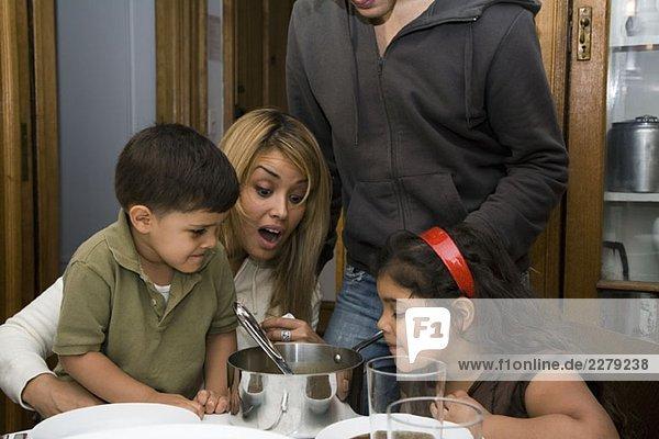 Eine Familie  die am Esstisch sitzt und schockiert aussieht.