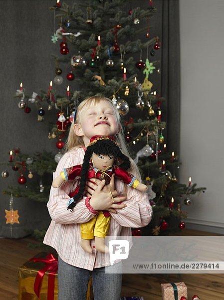 Ein Mädchen  das eine Puppe vor einem Weihnachtsbaum umarmt.