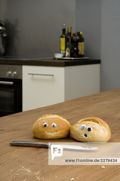 Two bread buns on a table with plastic eyeballs