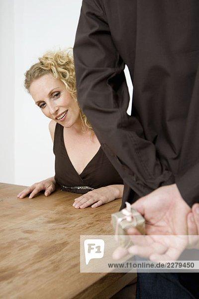 Eine Frau  die in den Händen eines Mannes auf die Gegenwart schaut.