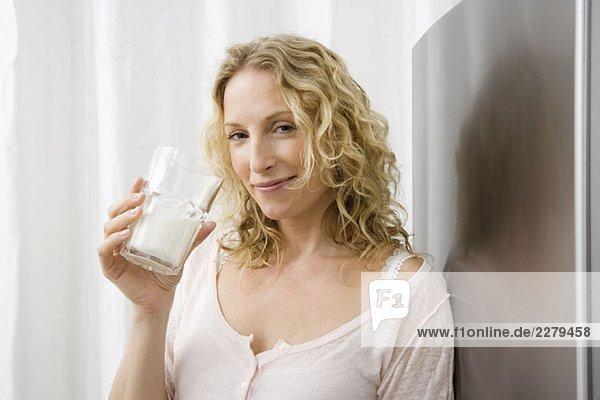 Eine Frau  die ein Glas Milch trinkt.