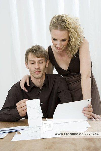 Ein mittleres erwachsenes Paar  das die Finanzen zu Hause erledigt.