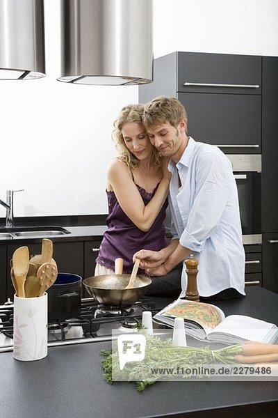 Ein mittleres erwachsenes Paar  das zusammen in einer häuslichen Küche kocht.