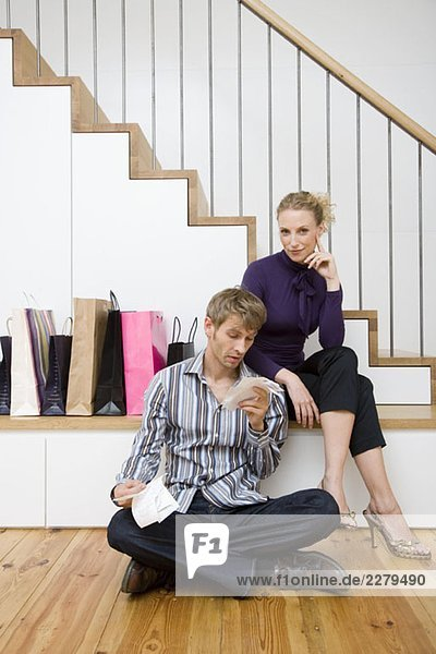 A mid adult man looking at receipts and a mid adult woman sitting next to six shopping bags