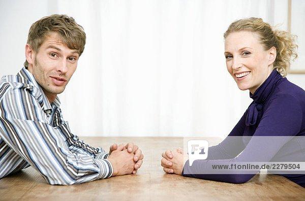 Ein erwachsenes Paar  das von Angesicht zu Angesicht sitzt und lächelt.
