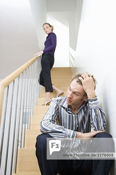 A mid adult couple arguing on a staircase