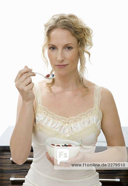 Eine Frau hält einen Löffel Joghurt und Himbeeren an den Mund.