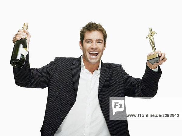 Junger Mann mit Filmpreis und Champagnerflasche  Portrait