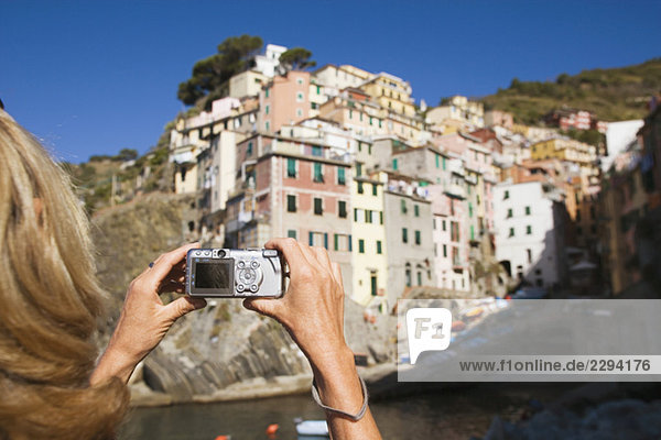 Italy  Liguria  Riomaggiore  Woman photographing houses