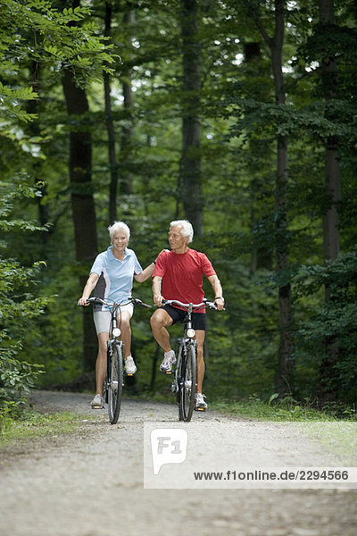 Seniorenpaar Radfahren auf Waldweg