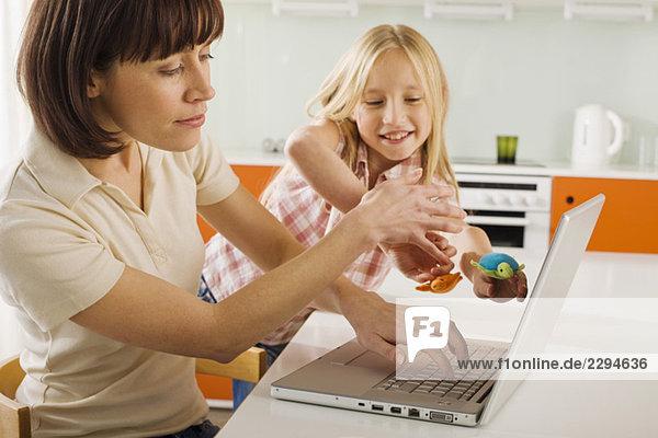 Mutter und Tochter (8-9) in der Küche  Mutter mit Laptop