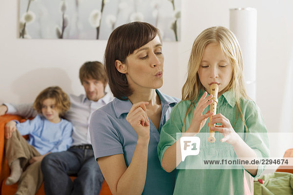 Mother and daughter (8-9)  playing recorder