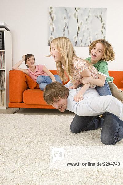 Junge (6-7) und Mädchen (8-9) auf dem Rücken des Vaters im Wohnzimmer