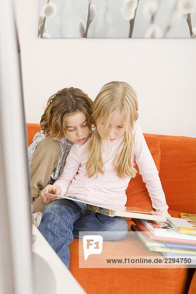 Brother and sister reading a book together