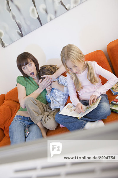 Mother and children watching television together
