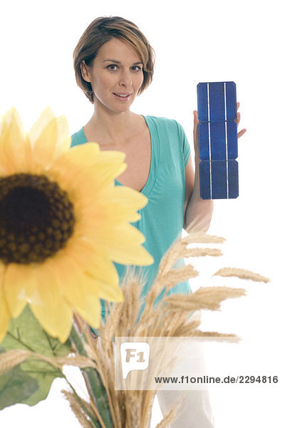 Woman holding solar cells  sunflower in foreground