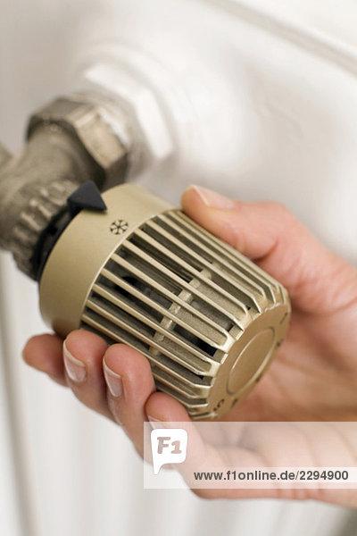 Weibliche Hand am Thermostat