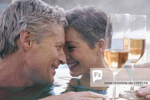 Erwachsenes Paar mit Champagner im Schwimmbad  Portrait