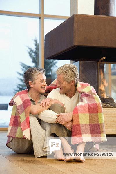 Erwachsenes Paar sitzt vor dem Kamin