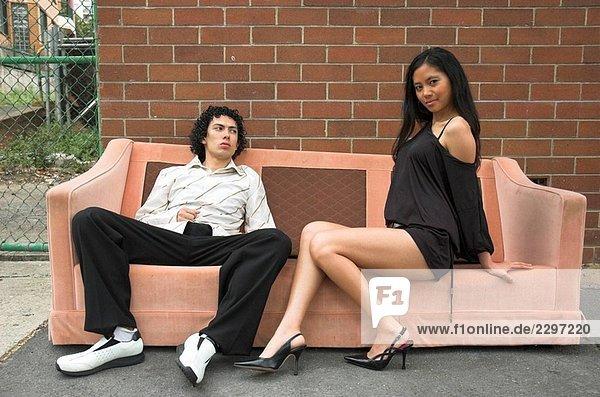 Zwei junge Partypeople stellen auf eine alte Sofa in der Straße