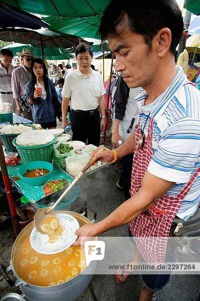Thai Jüngling Vorbereitung Curry Suppe mit Frikadellen und Reis Nudeln auf einer Straße Markt nah an dem Königspalast in Bangkok  der Stadt der Engel  Thailand  Südost-Asien
